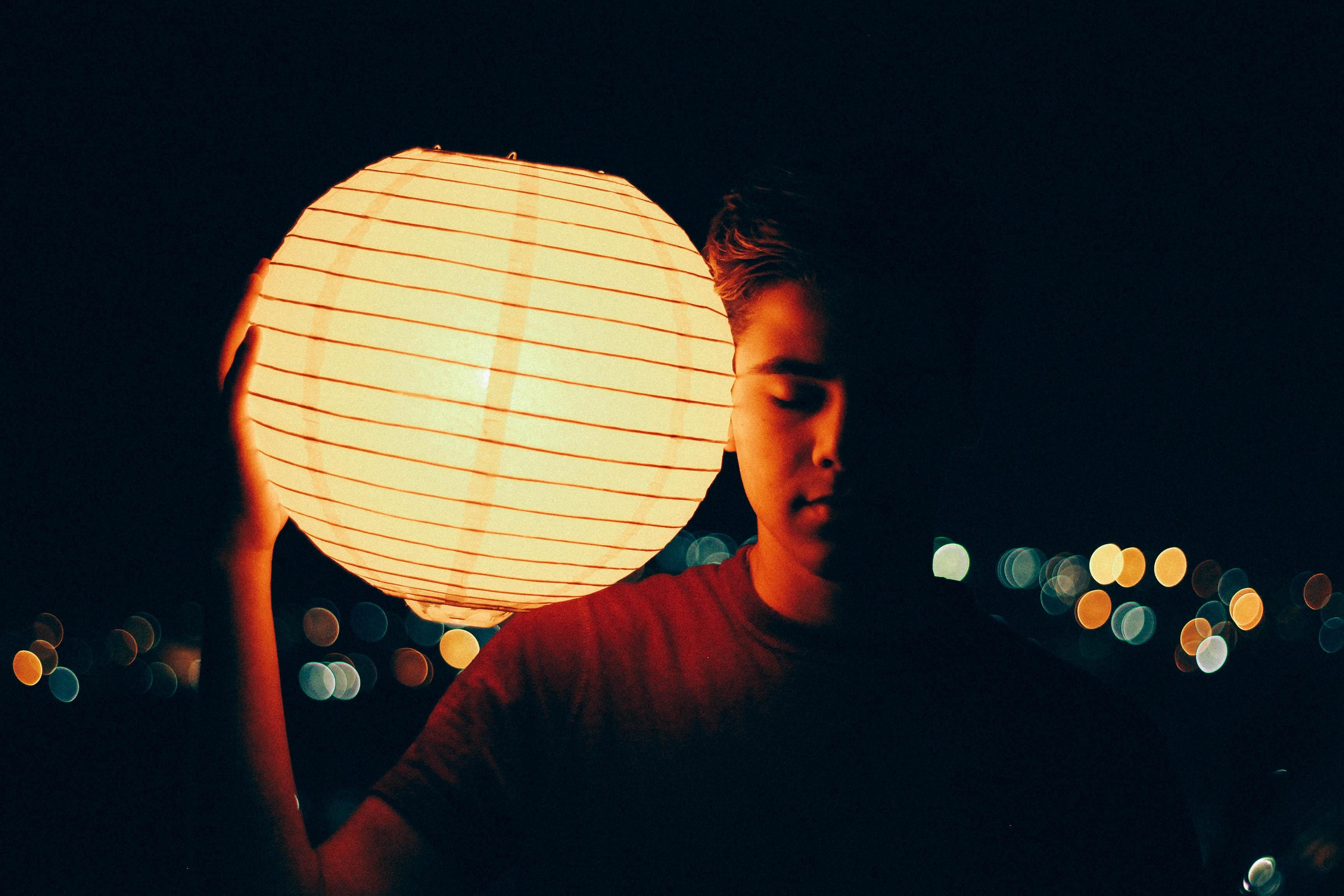 man holding lantern during nighttime