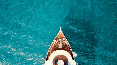 birds eye photography of boat on body of water luxury teams background