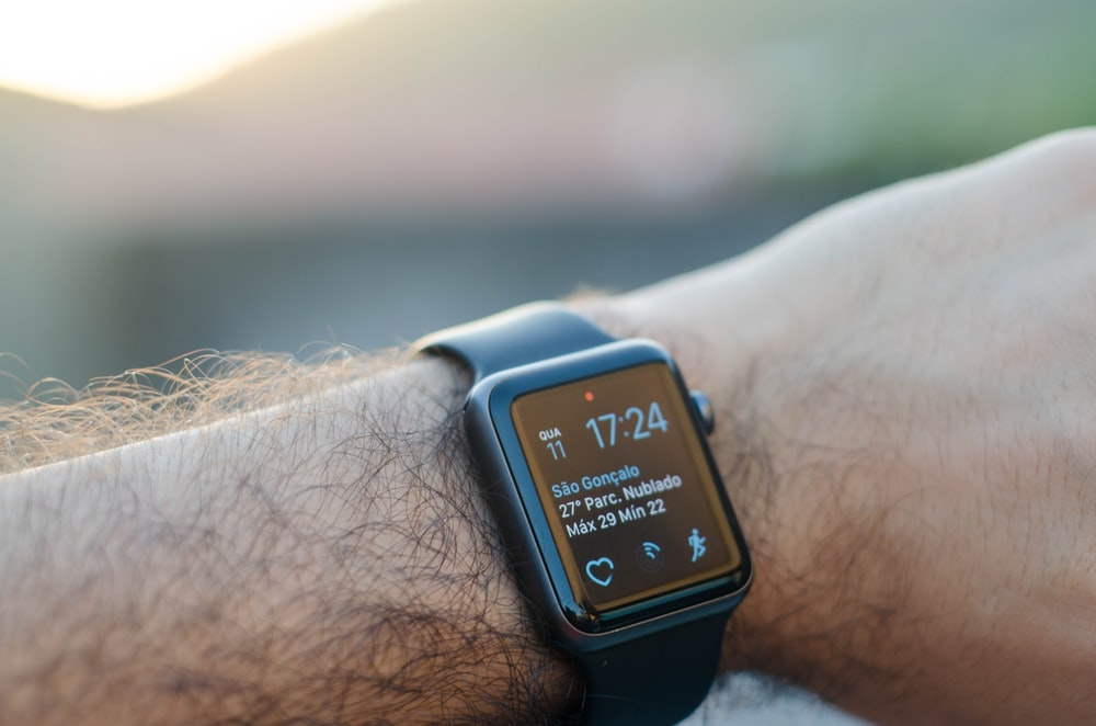 person wearing black smartwatch with black band