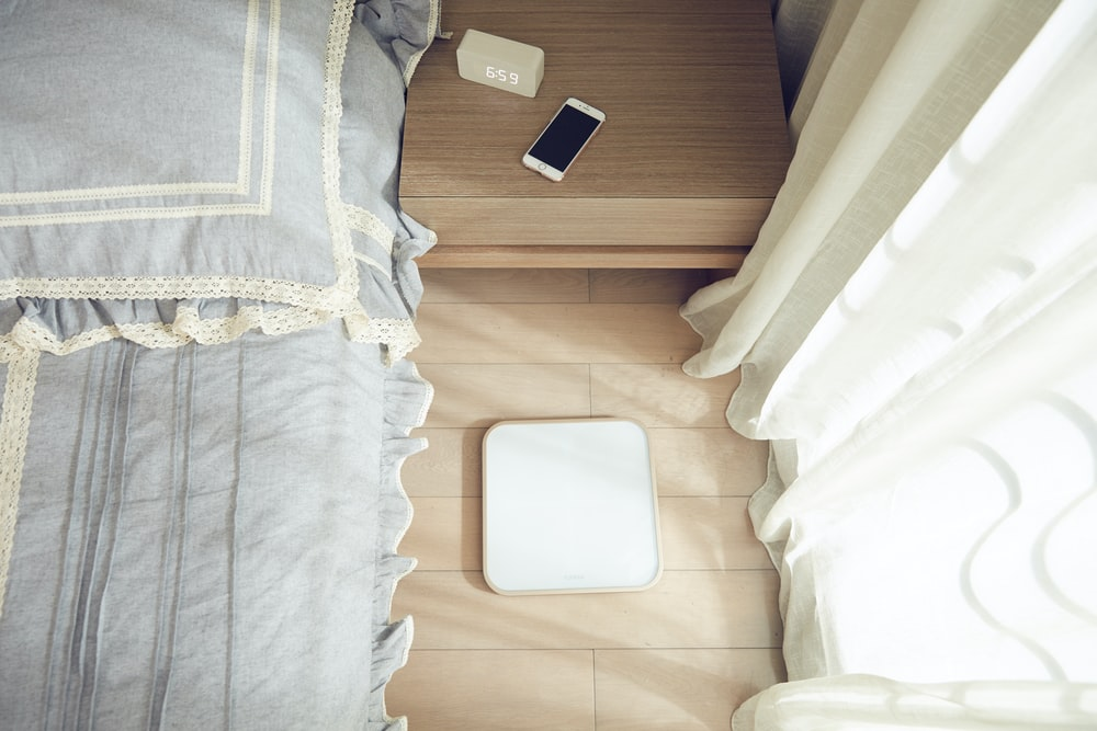 smartphone on brown side table beside bed