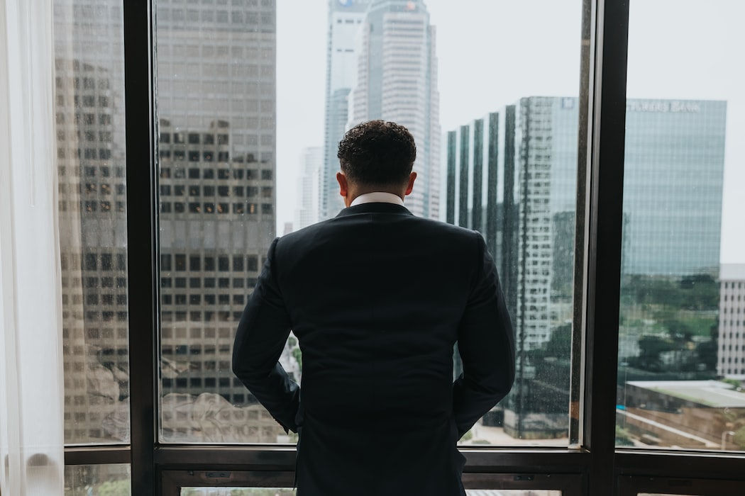 Man looking out the window of a highrise
