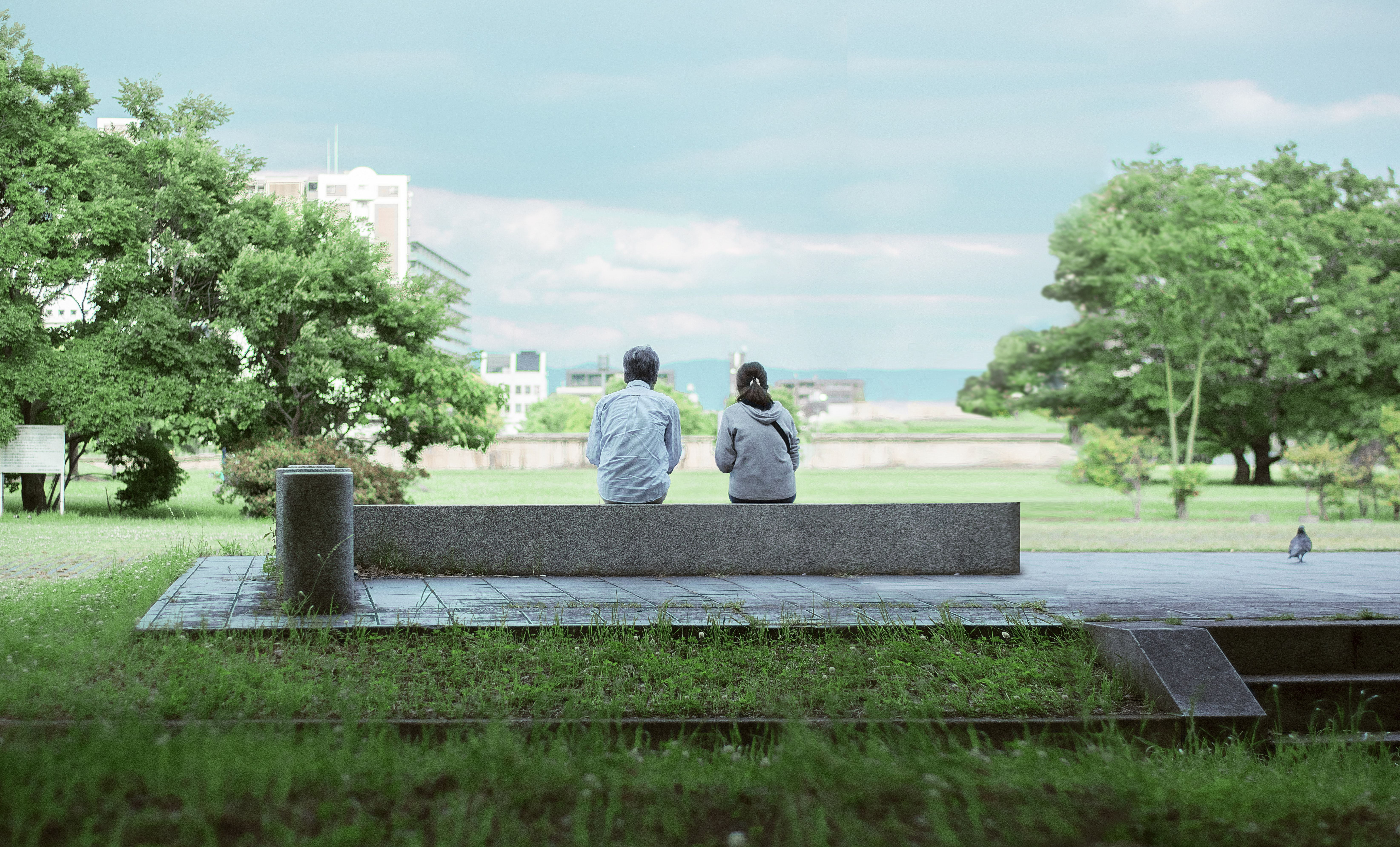 two person sitting on concrete bench