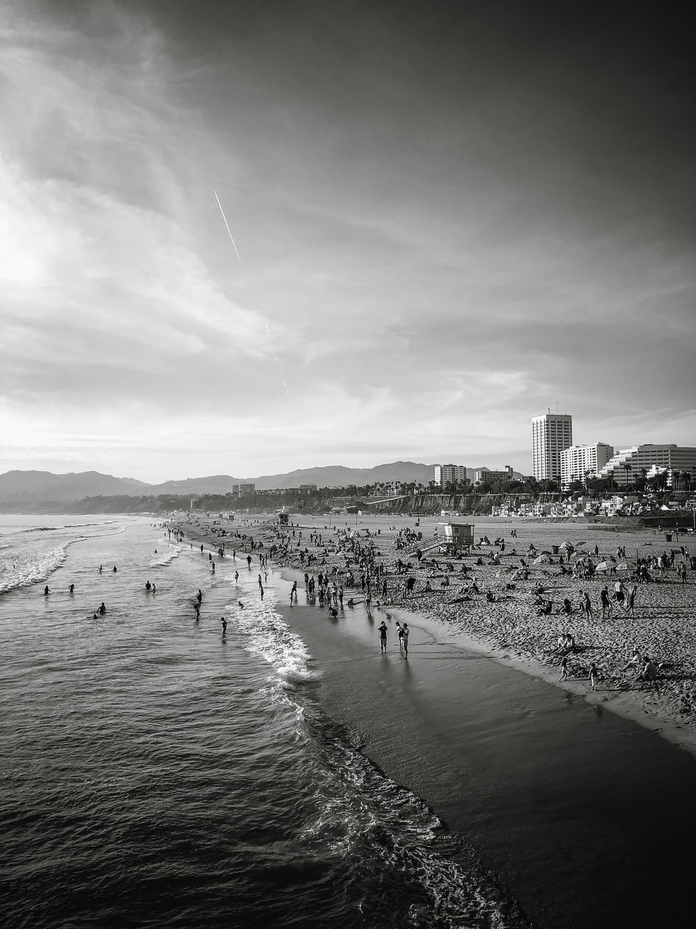 grayscale photography of people gathered near shore
