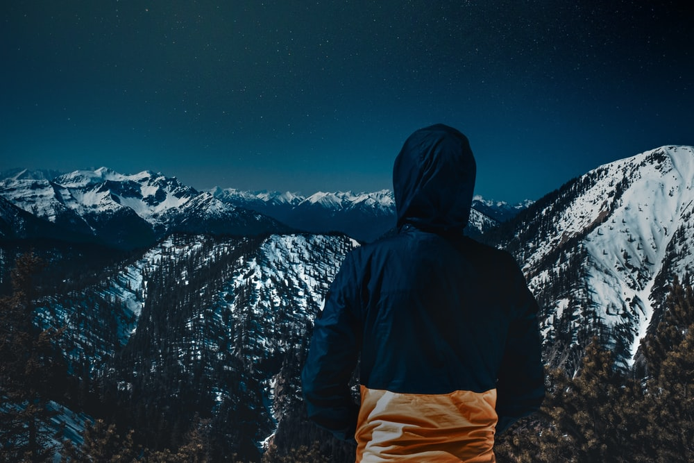 person wearing jacket facing mountains