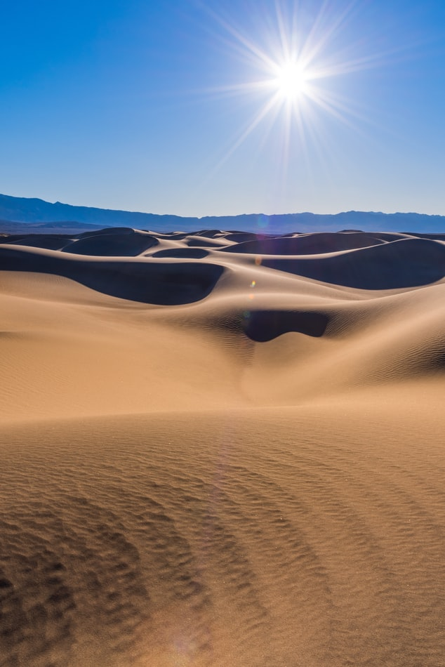 the sun shining over the Mesquite Sand Dunes