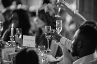 grayscale photo of people rising a drinking glasses