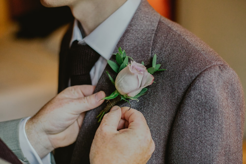 person putting pink rose pin on person's notched lapel suit jacket