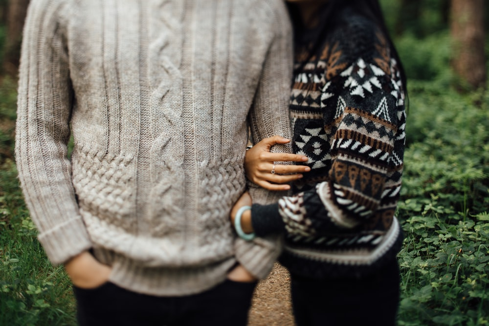 woman in black and white sweater hugging man in gray cable knit sweater