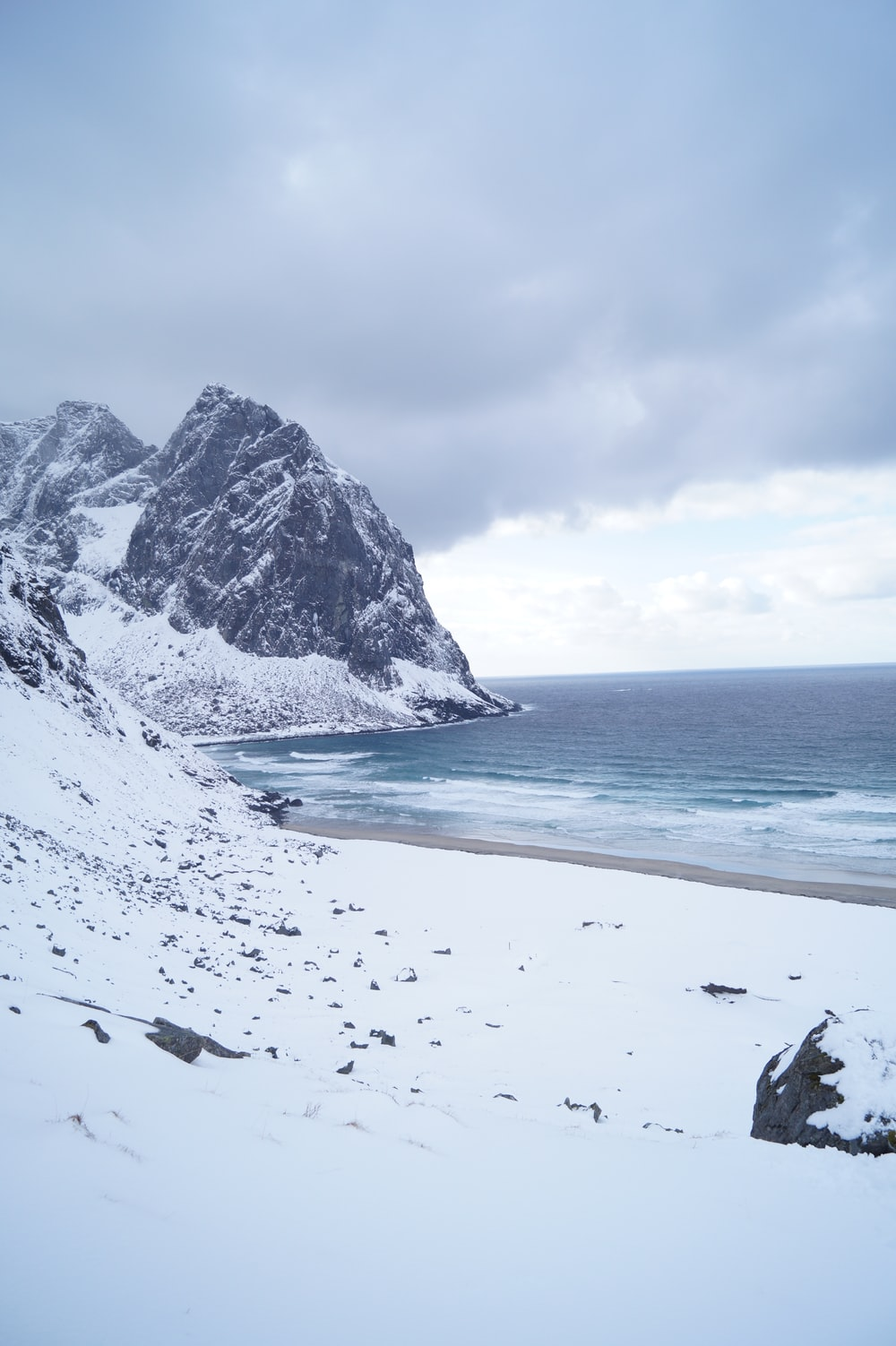 snow covered mountains on shore under gray sky