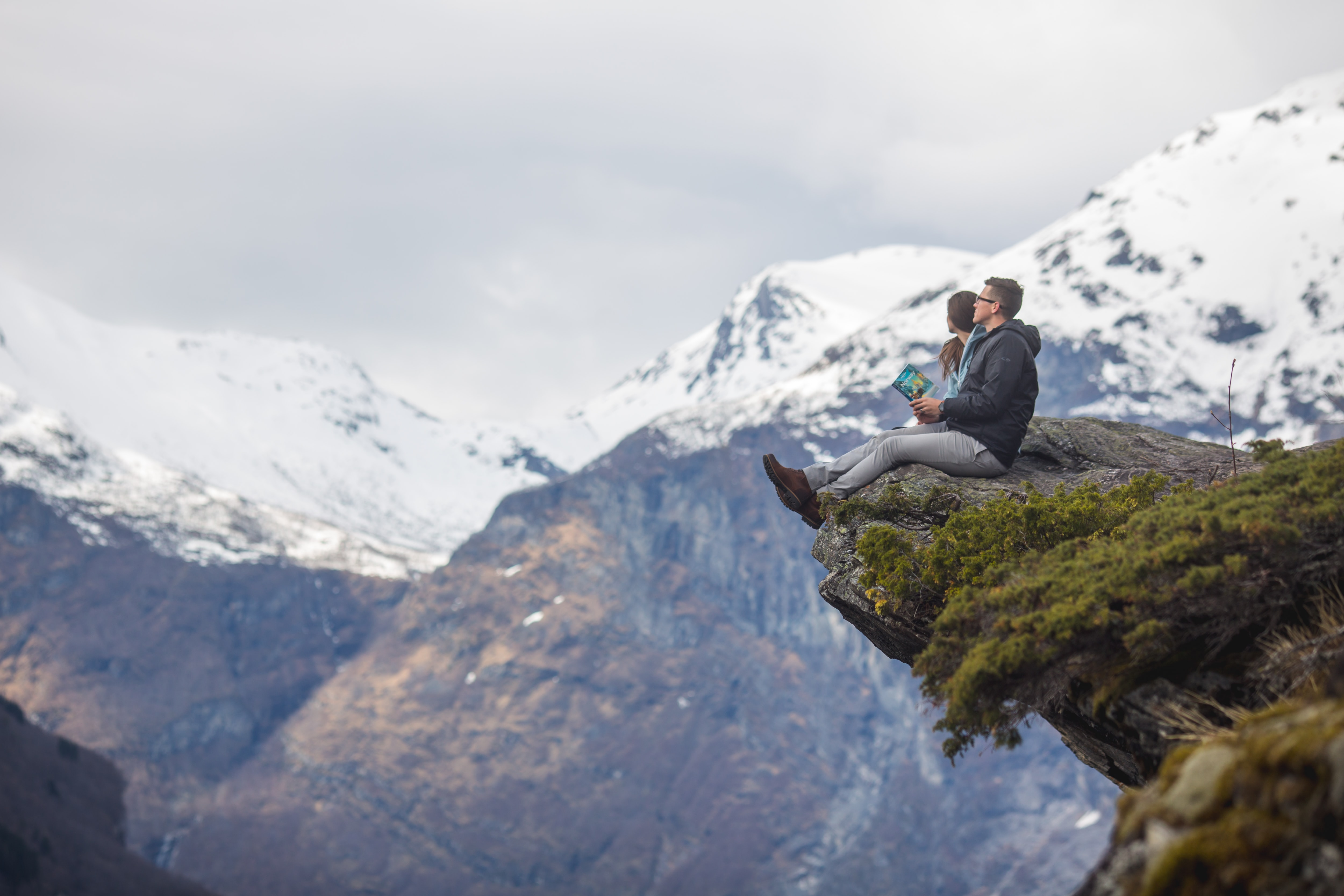 man and woman sitting on cliff at daytime