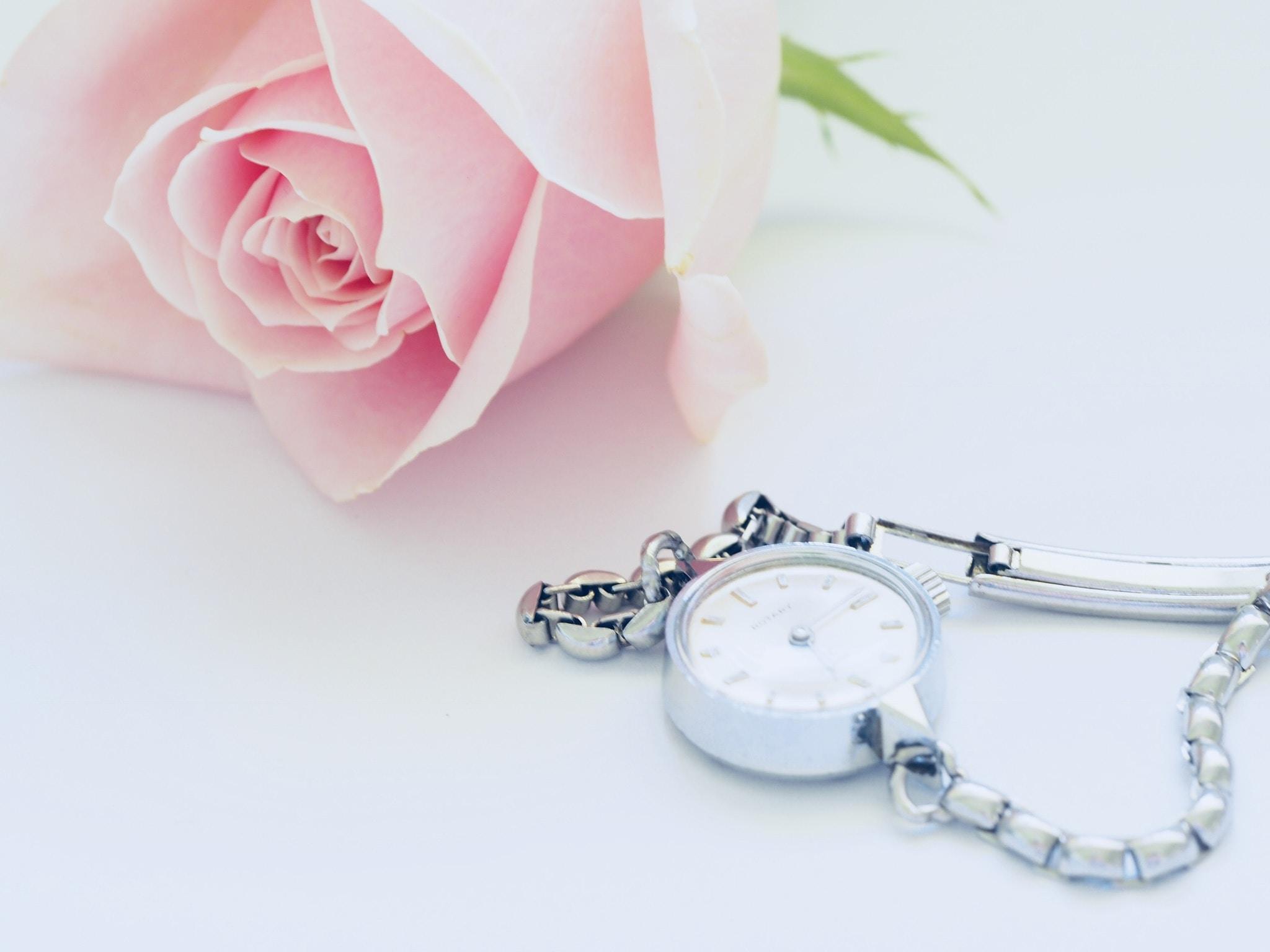 round white analog watch beside pink rose