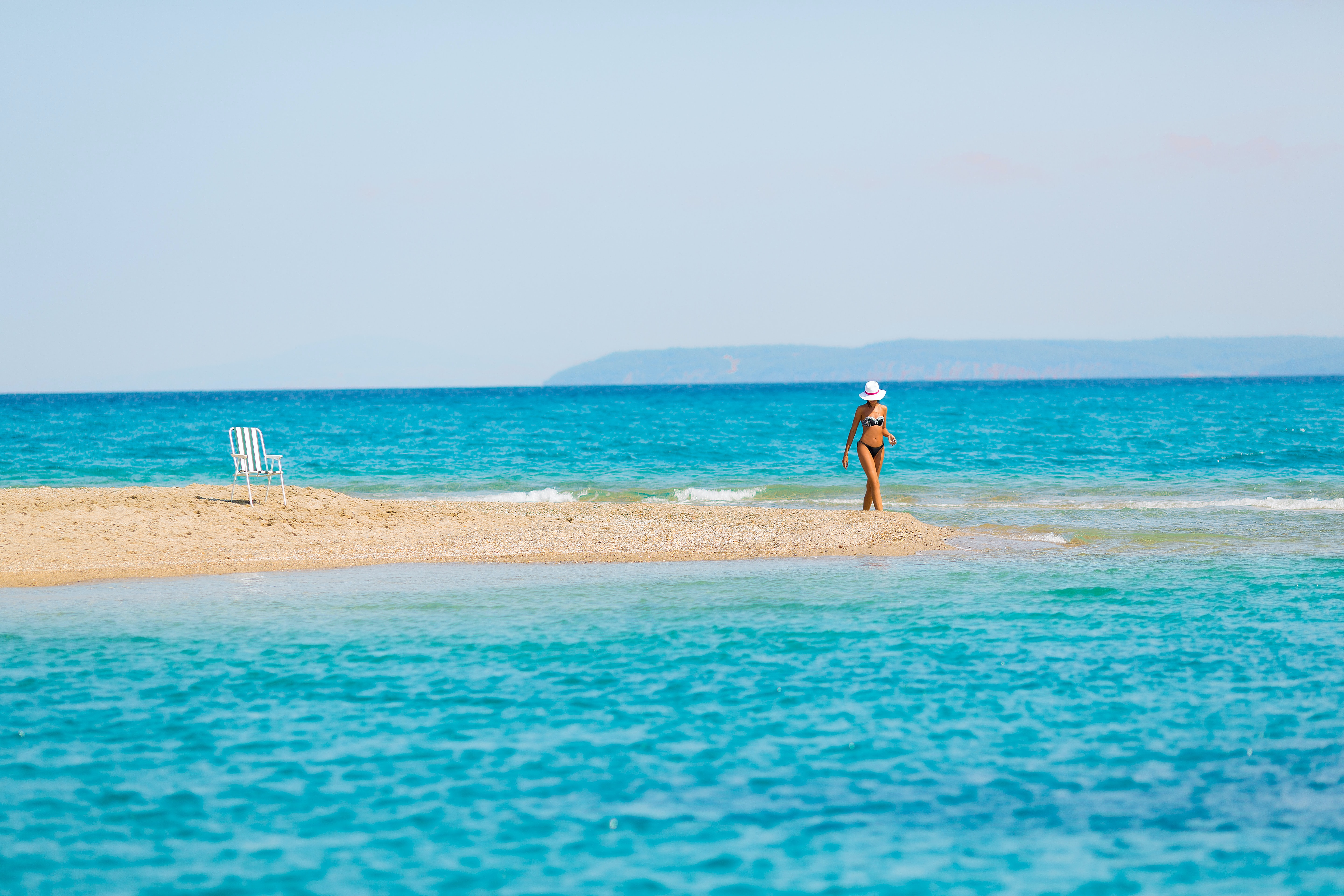 woman standing on sand bar during daytime