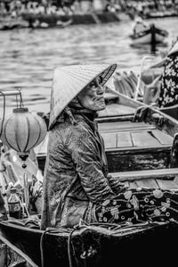 person in cone hat riding boat grayscale photography