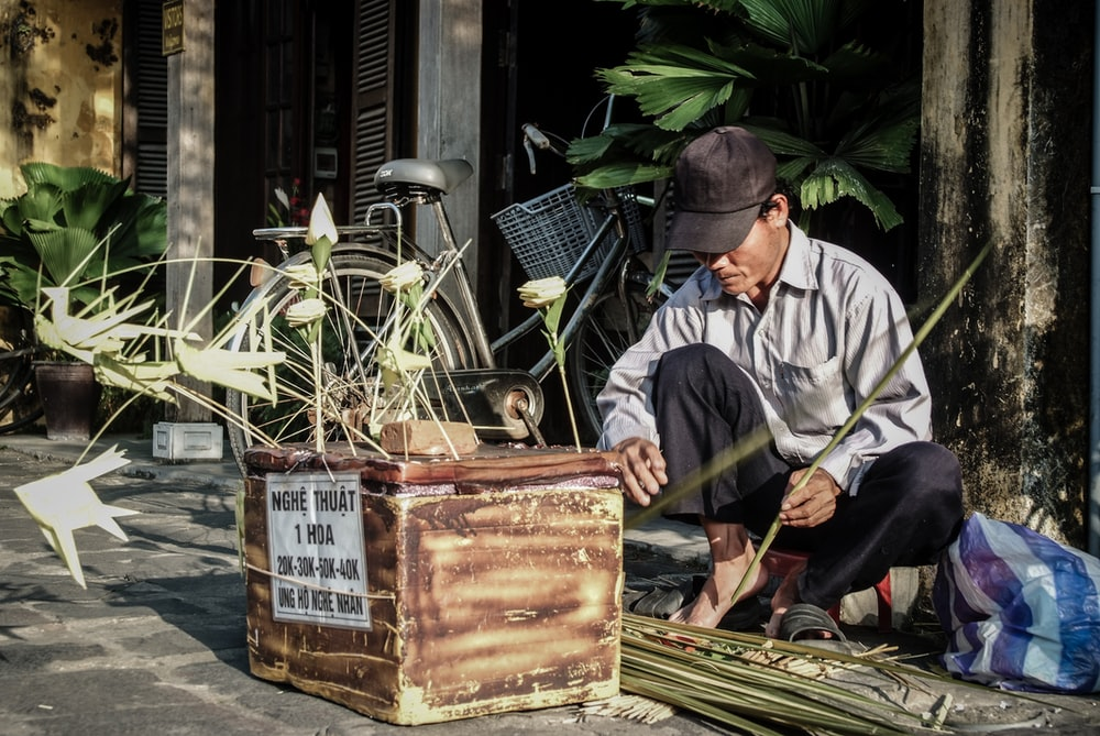 man in gray dress shirt making leaf craft