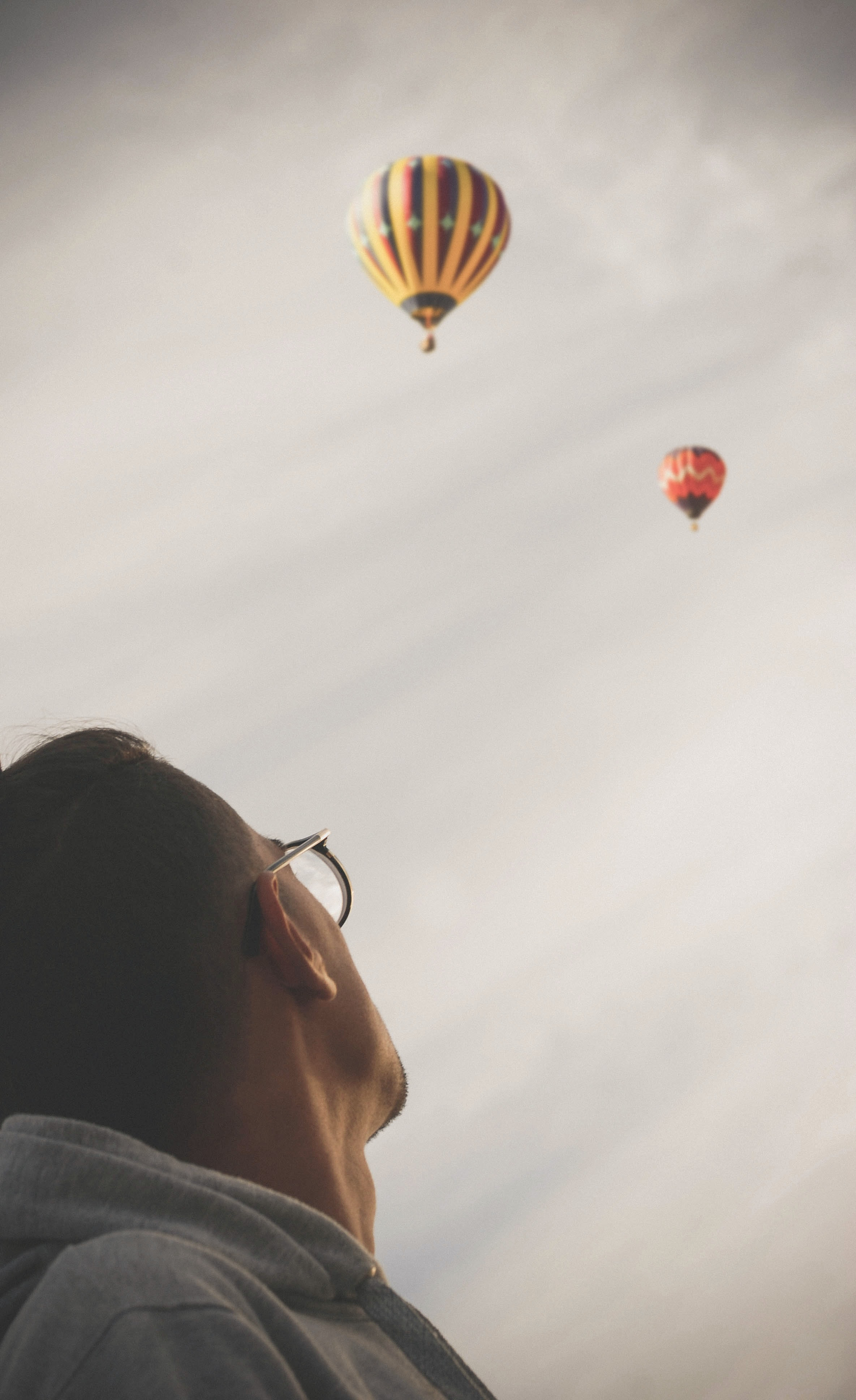man looking at two hot air balloons in the sky