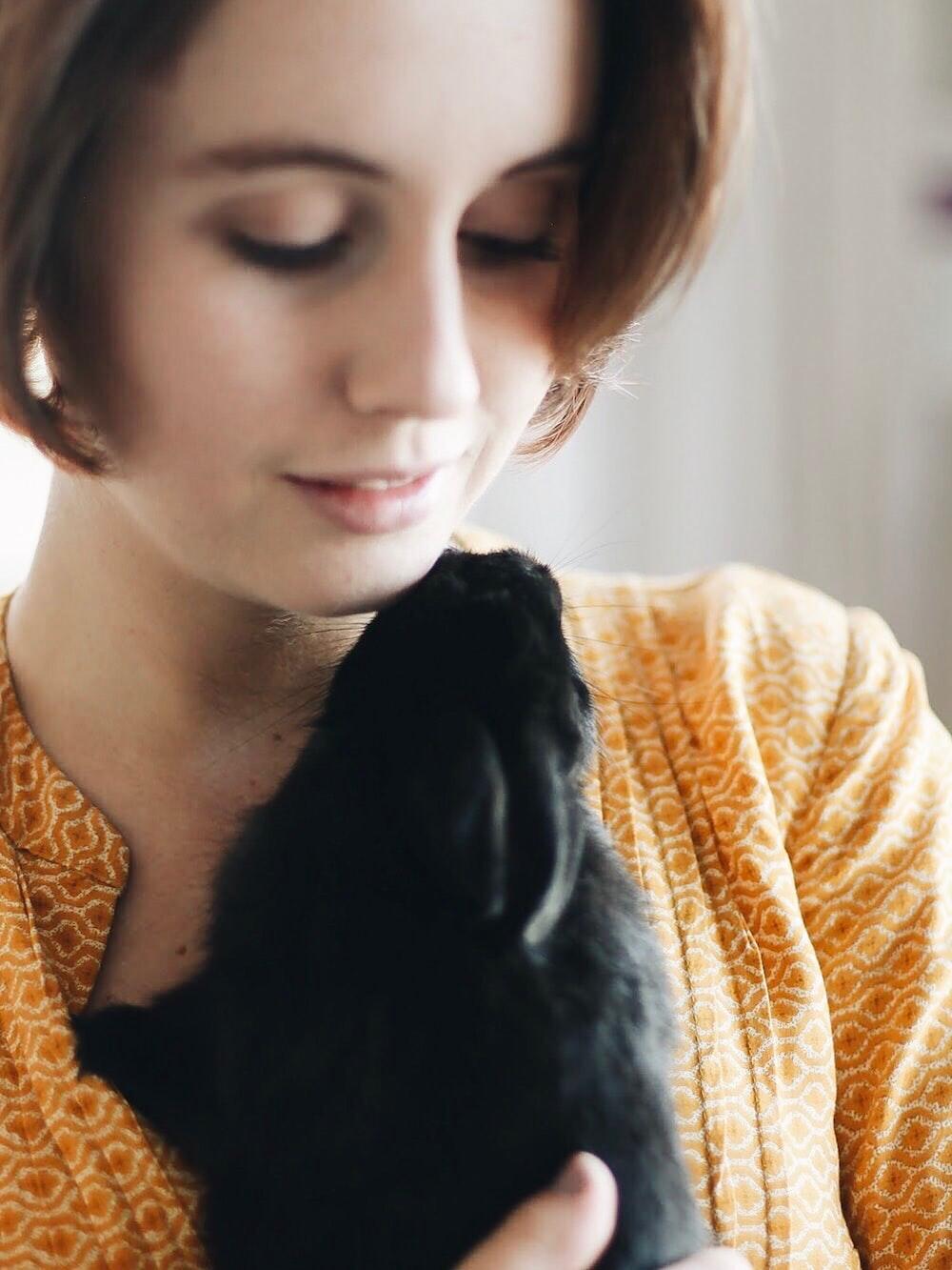 woman carrying black dog