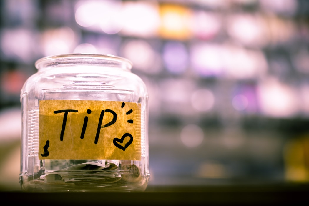 A tip jar about halfway filled with a very blurry background