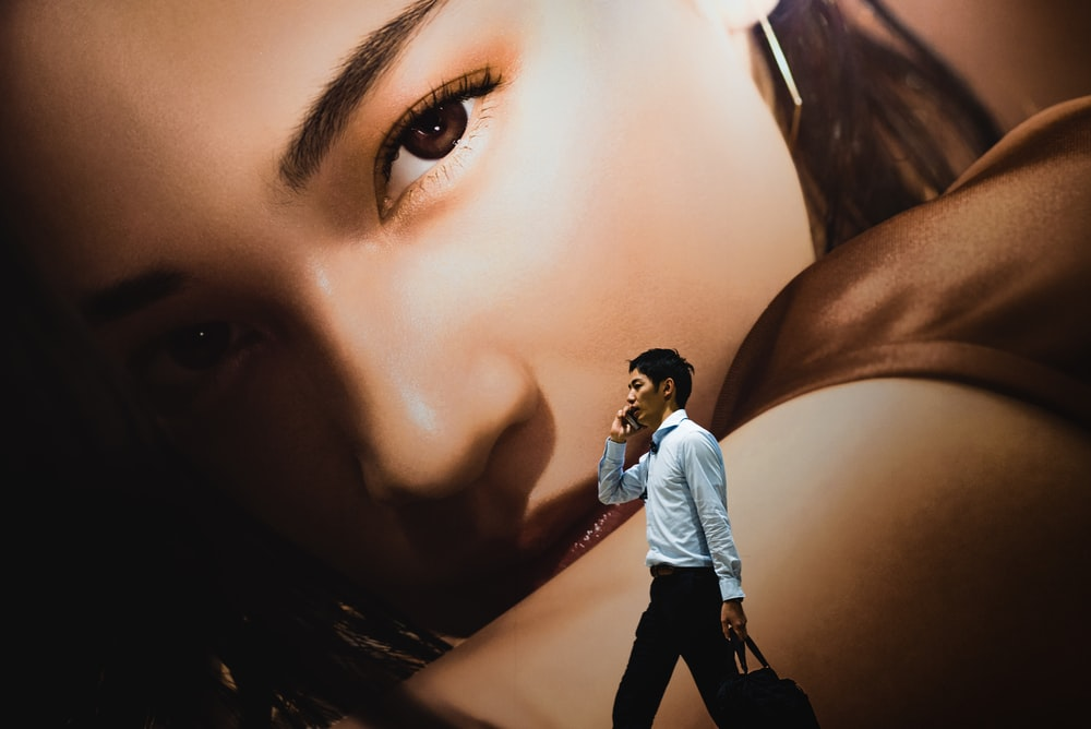 man walking while holding smartphone near woman-themed wall painting