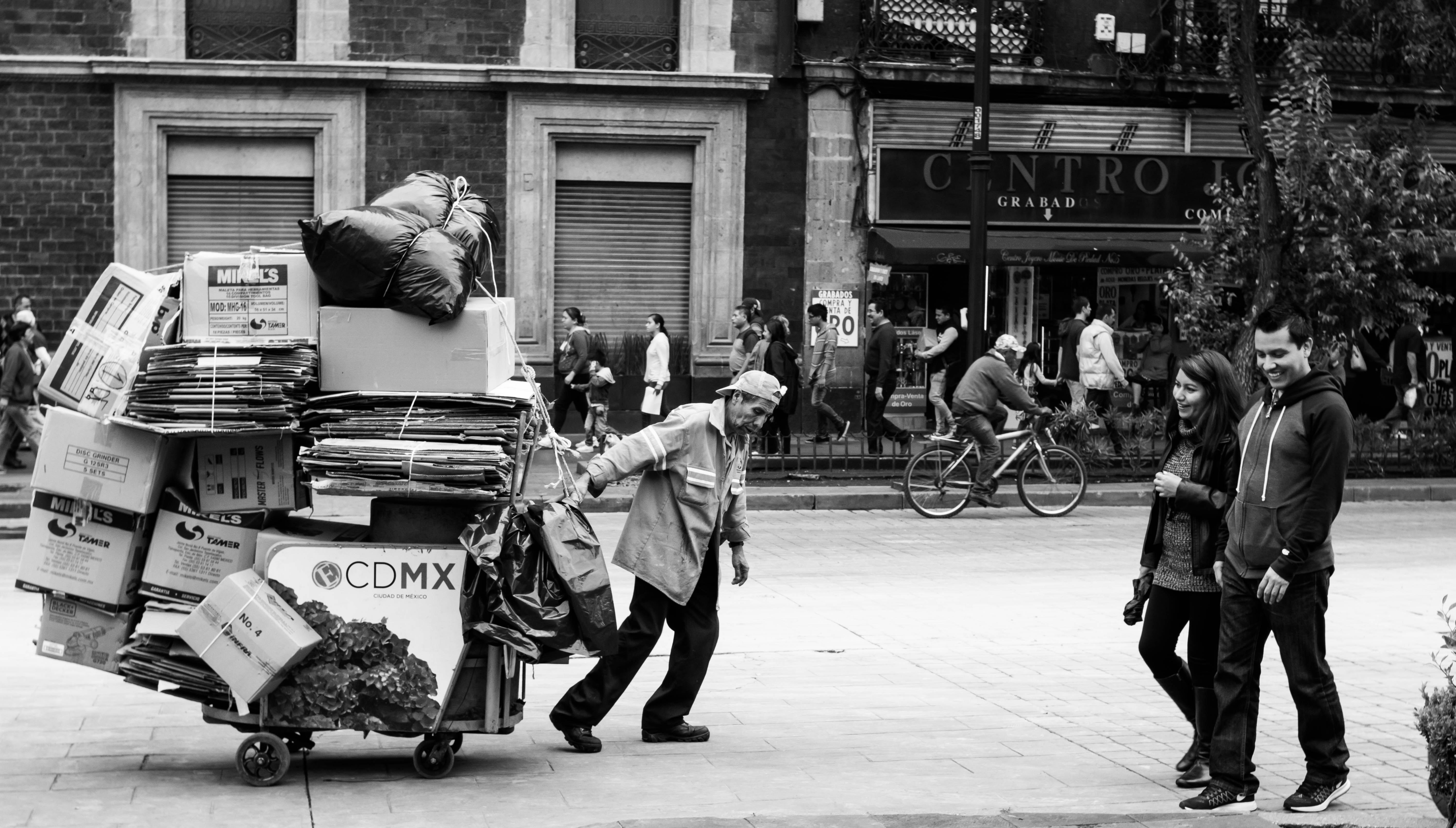 man dragging wagon with cardboard boxes