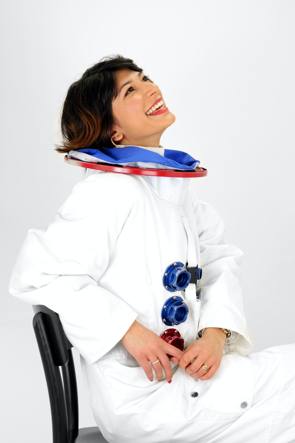 woman wearing astronaut suit smiling while sitting on chair and looking up