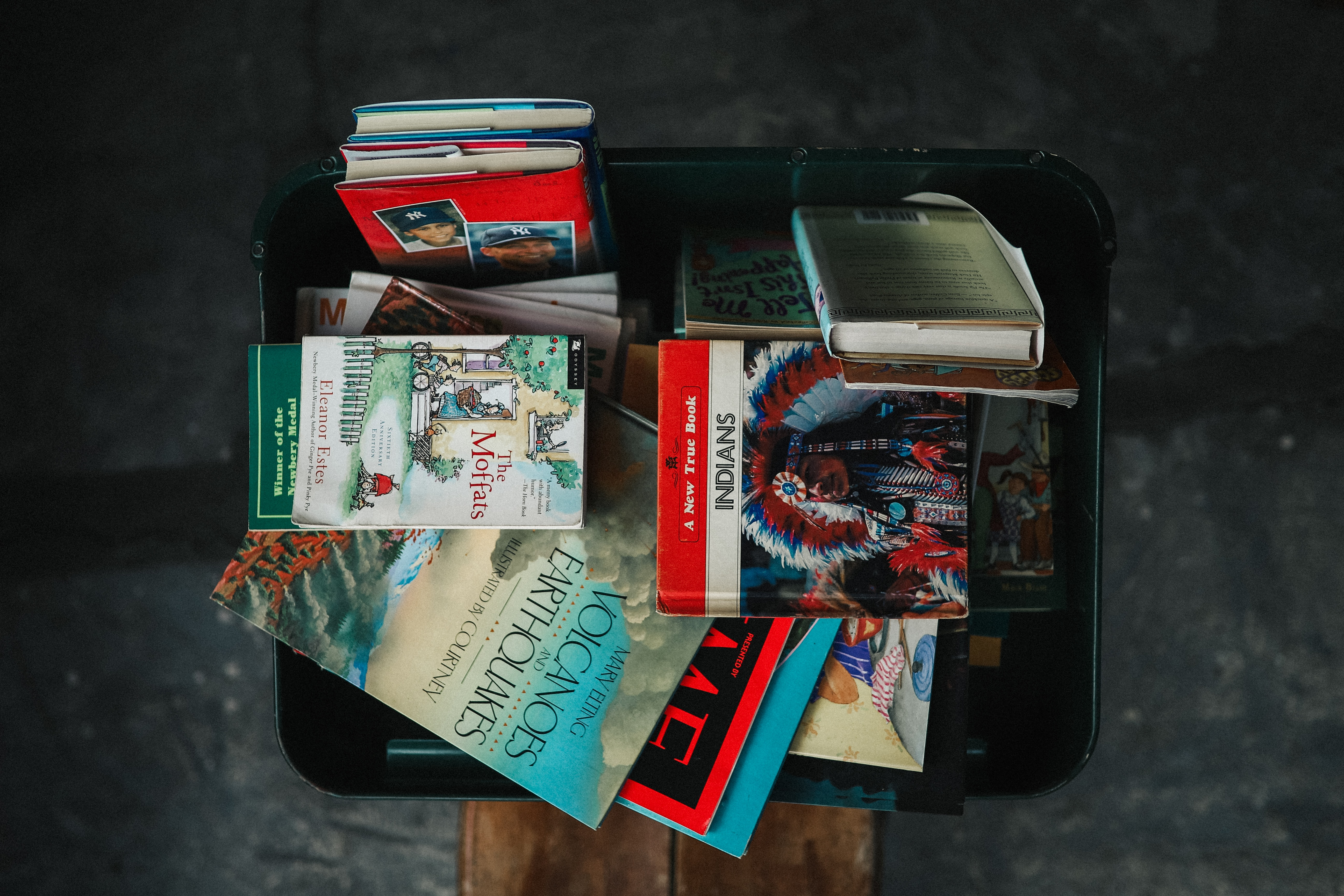 assorted books in black storage box in top view photography