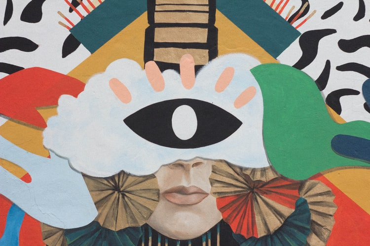 A photo of an abstract painted mural that shows the lower half of a woman's face with clouds and fans around it.