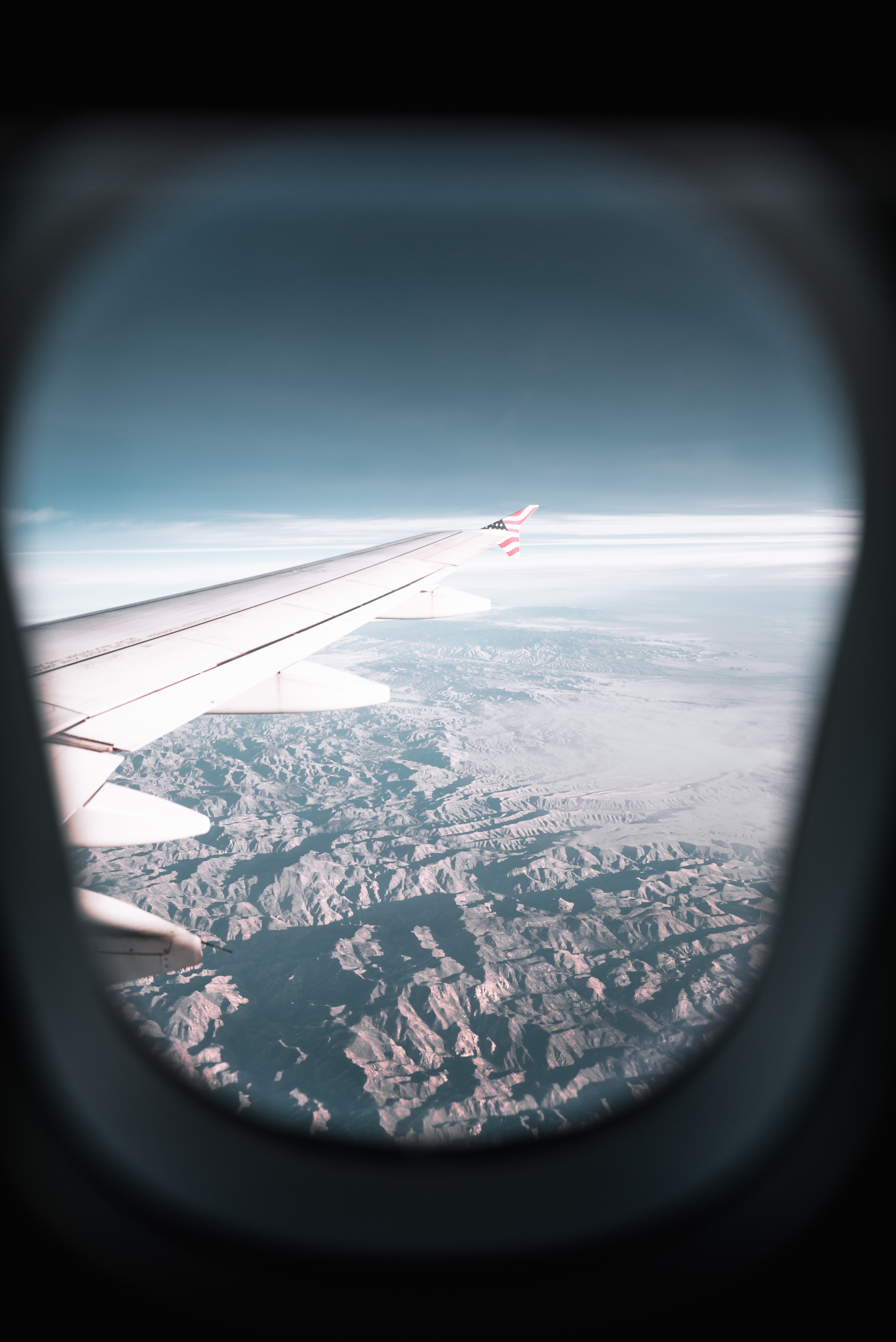 airplane window view of airplane's wing and mountains during day