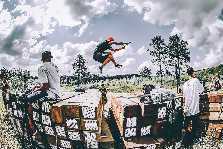 man leaping on brown wooden platform
