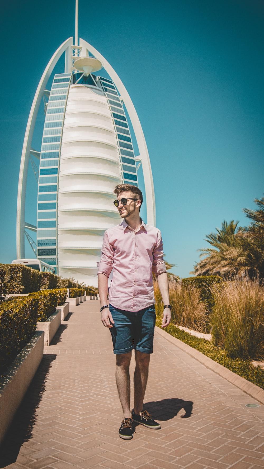 man walking on pathway near Burj Al, Dubai