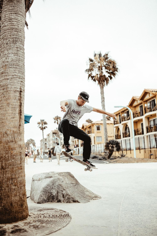 man playing skateboard tricks on the rock during daytime