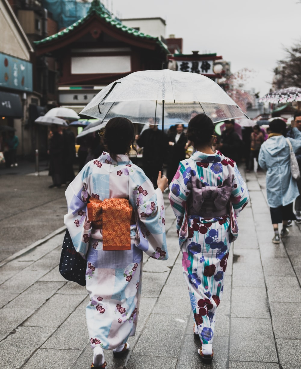two women wearing kimono under the umbrella