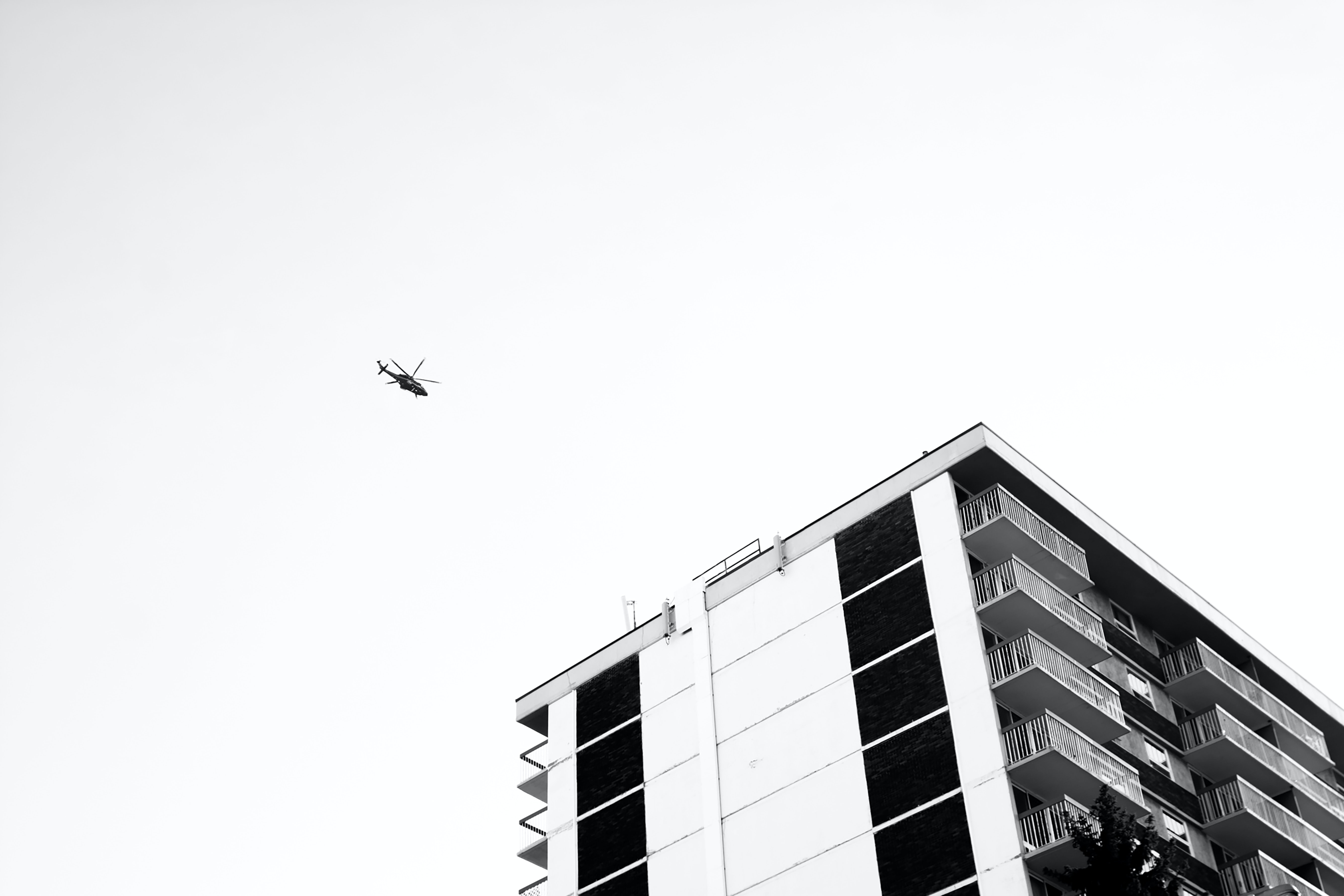 grayscale photo of airplane and building