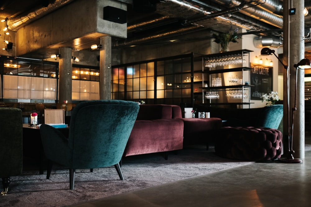 maroon and teal suede couches under brown roof