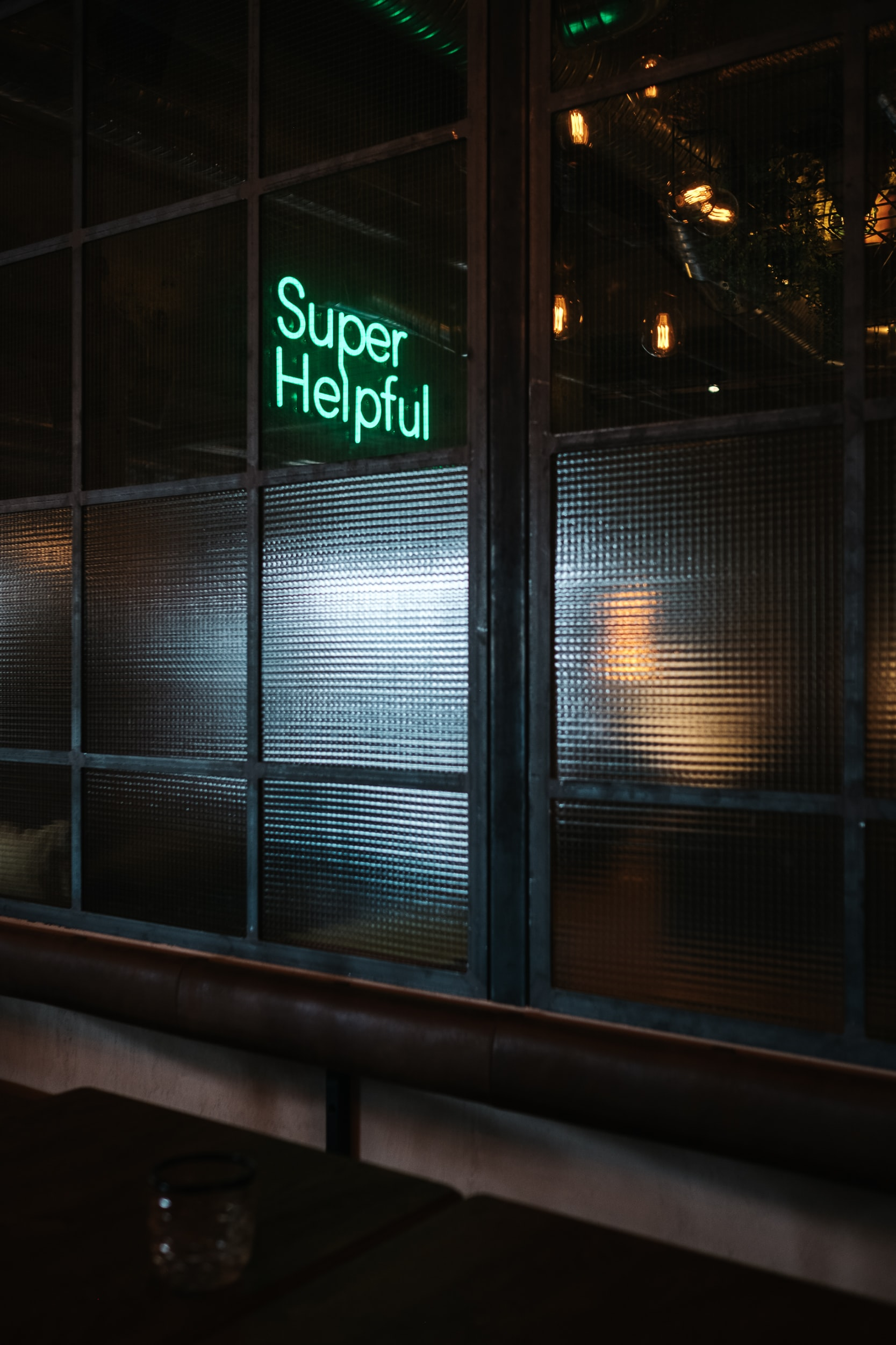 green Super helpful neon signage near window