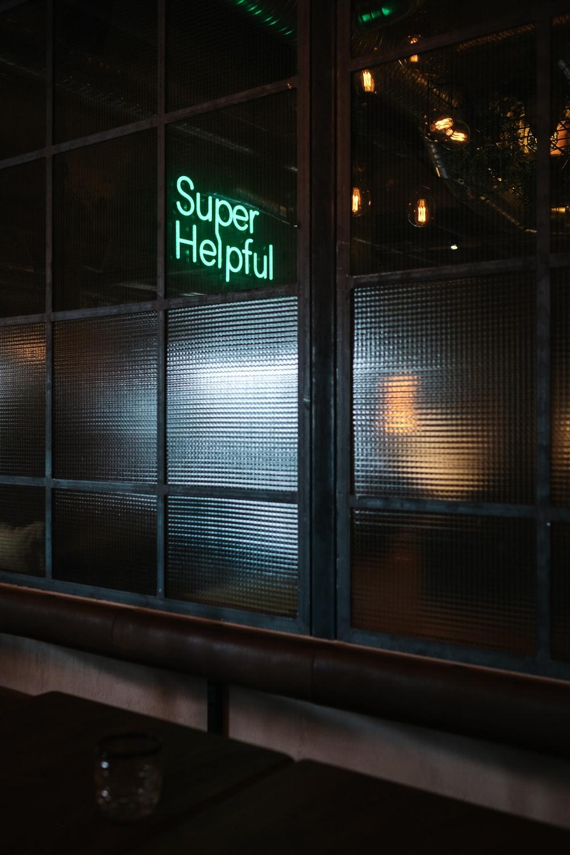 green Super helpful neon signage near window