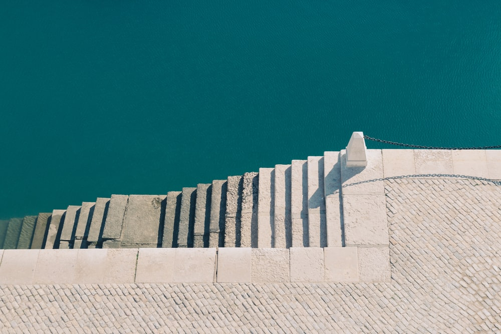white concrete stairs near body of water