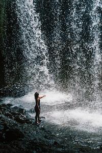 woman standing beside waterfalls