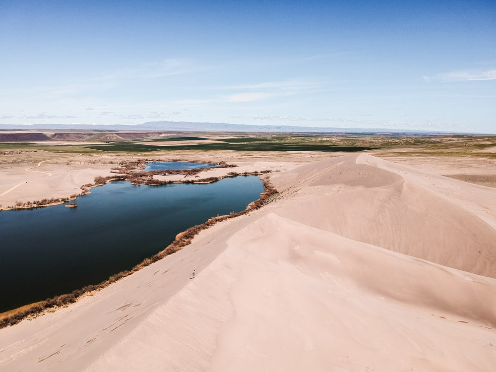 desert beside body of water during day time