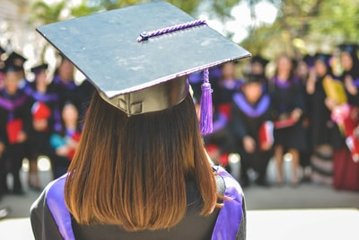 woman wearing academic cap and dress selective focus photography graduation teams background