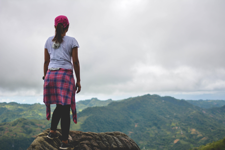 woman standing on mountain peak facing green mountains at daytime