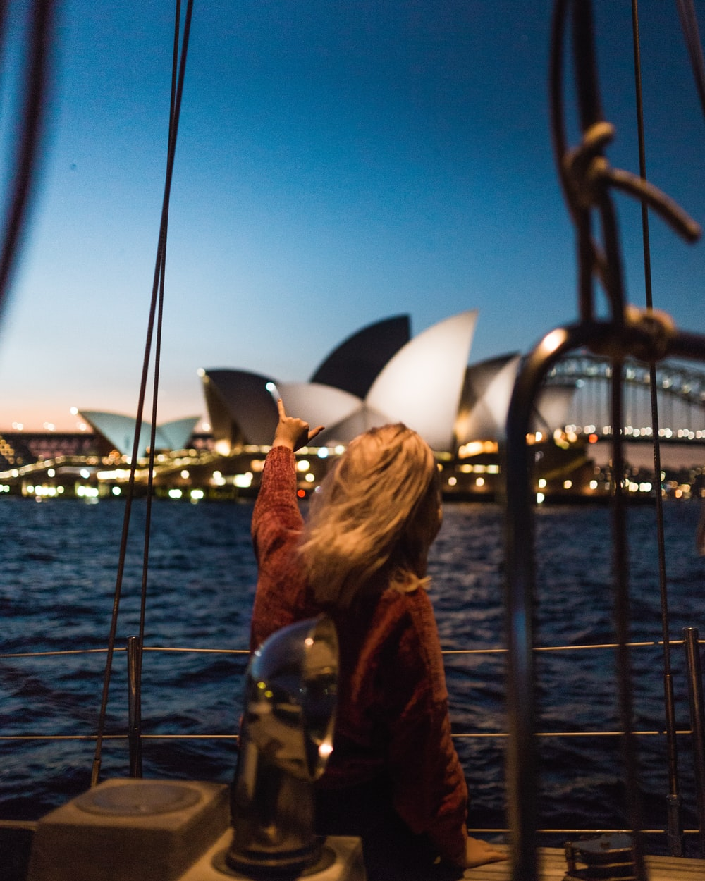 woman standing on boat looking at Sydney Opera House