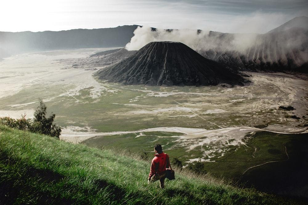 person standing on grass field near mountain