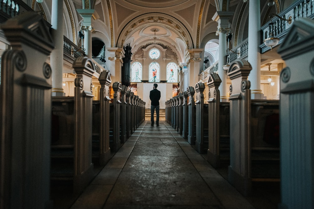 man standing between church pews
