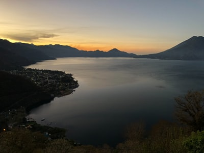 body of water between mountain at golden hour guatemala teams background