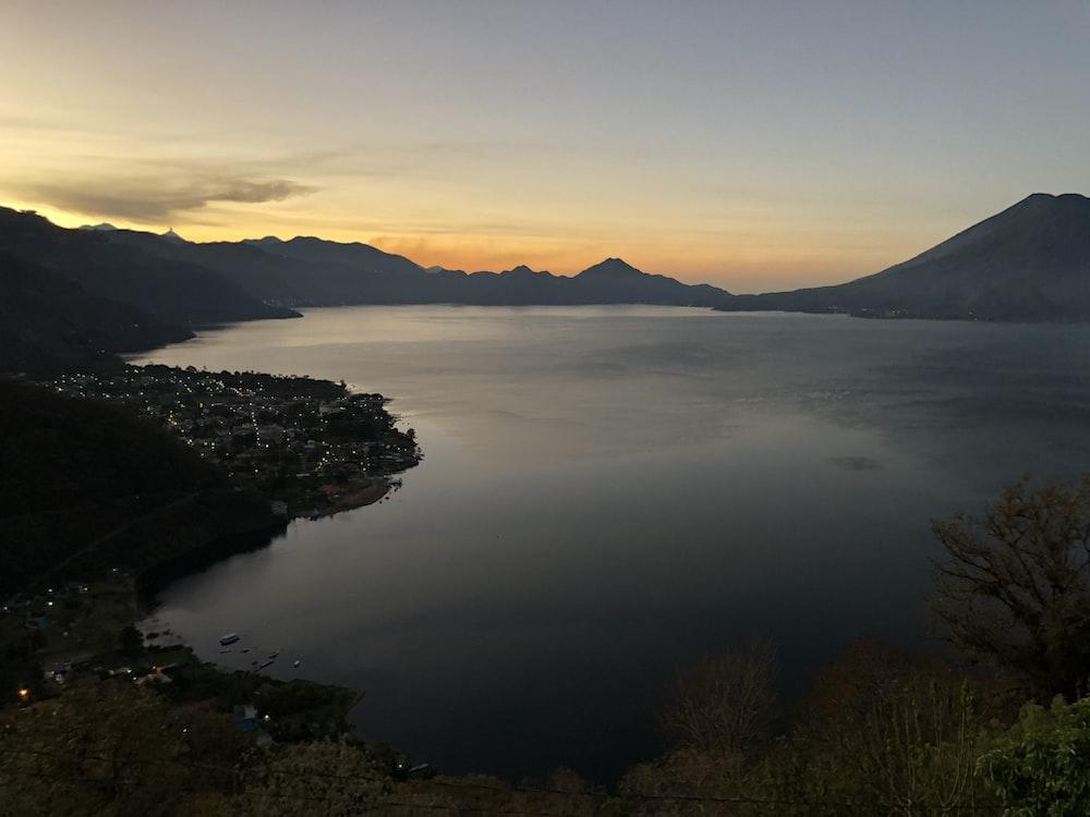 body of water between mountain at golden hour