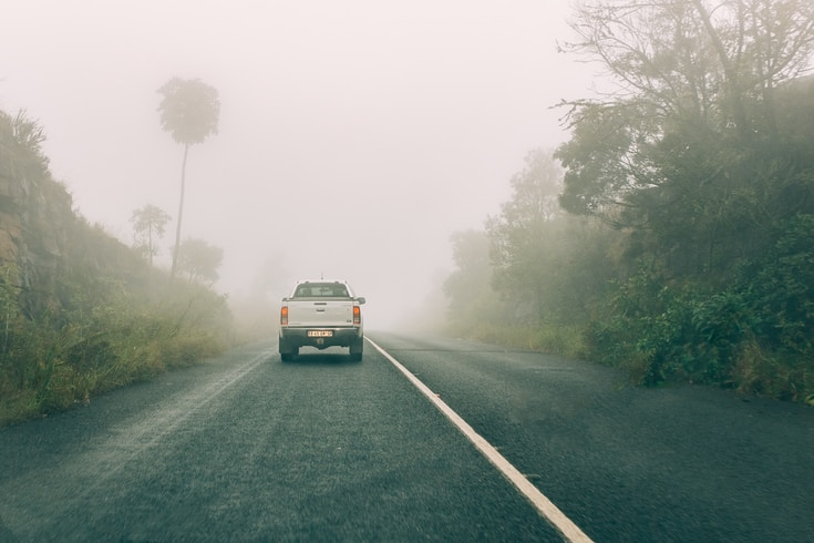 white van on road during foggy weather