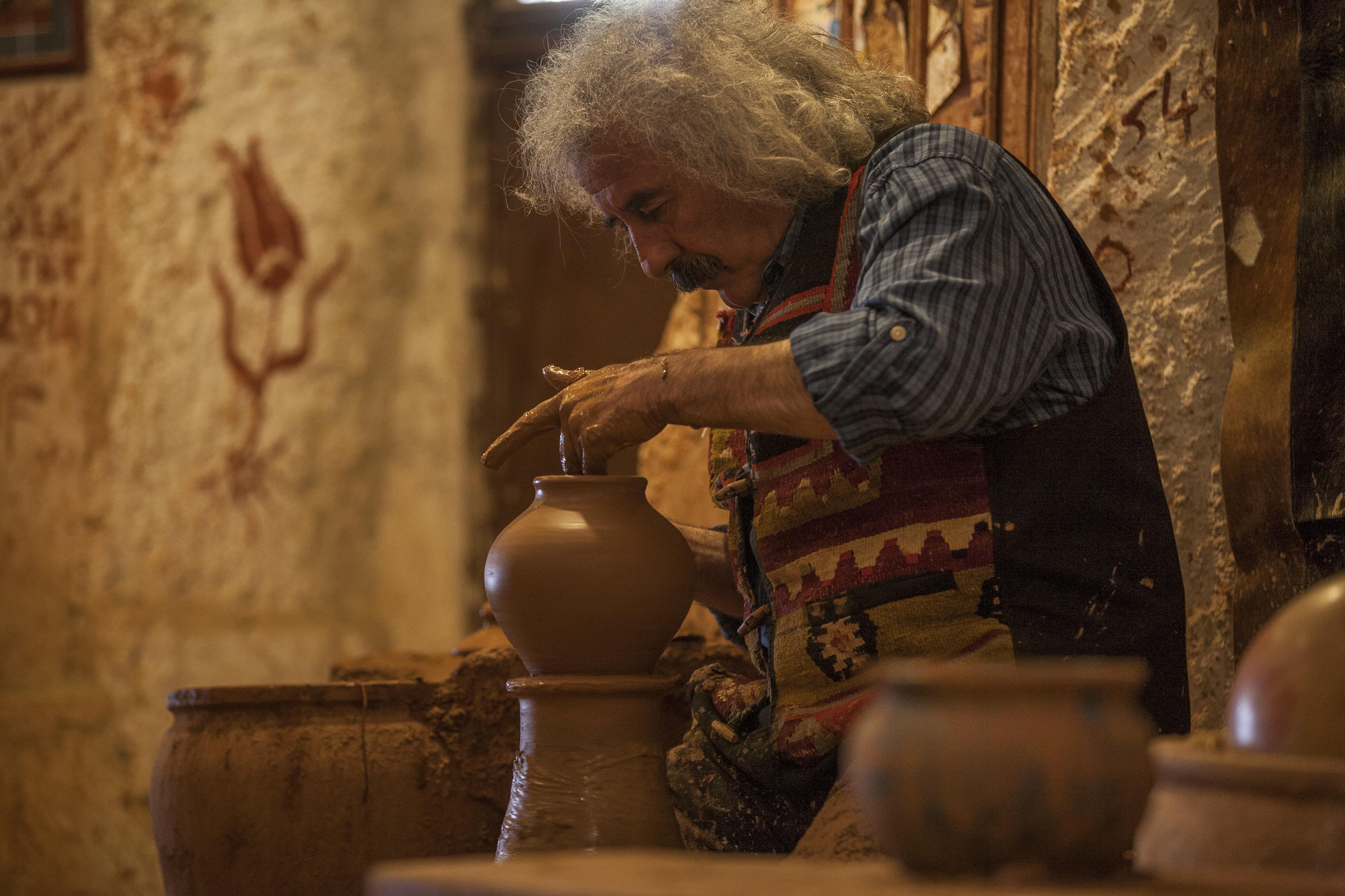 man making pot near wall in house