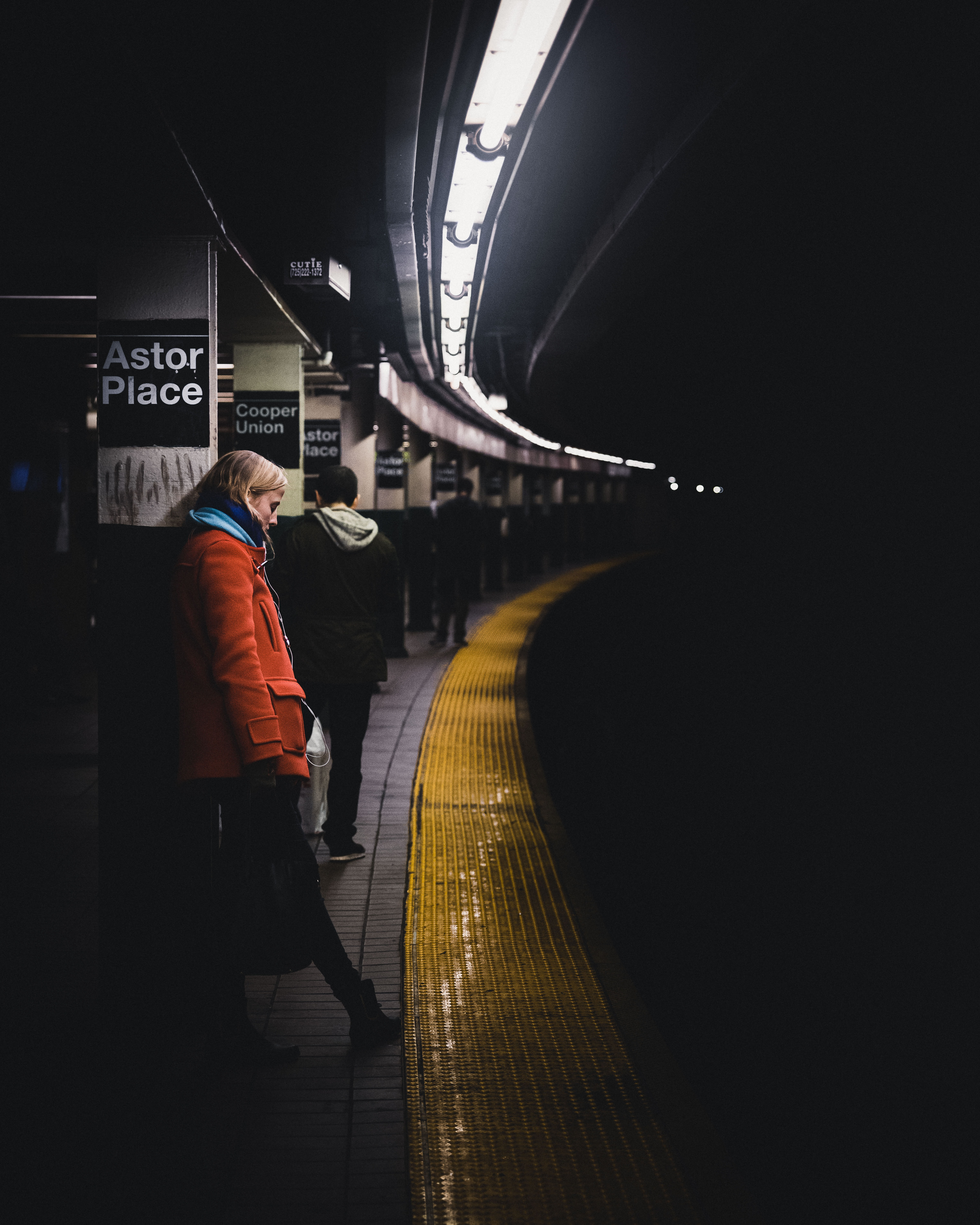 woman wearing red coat leaning on column on train station
