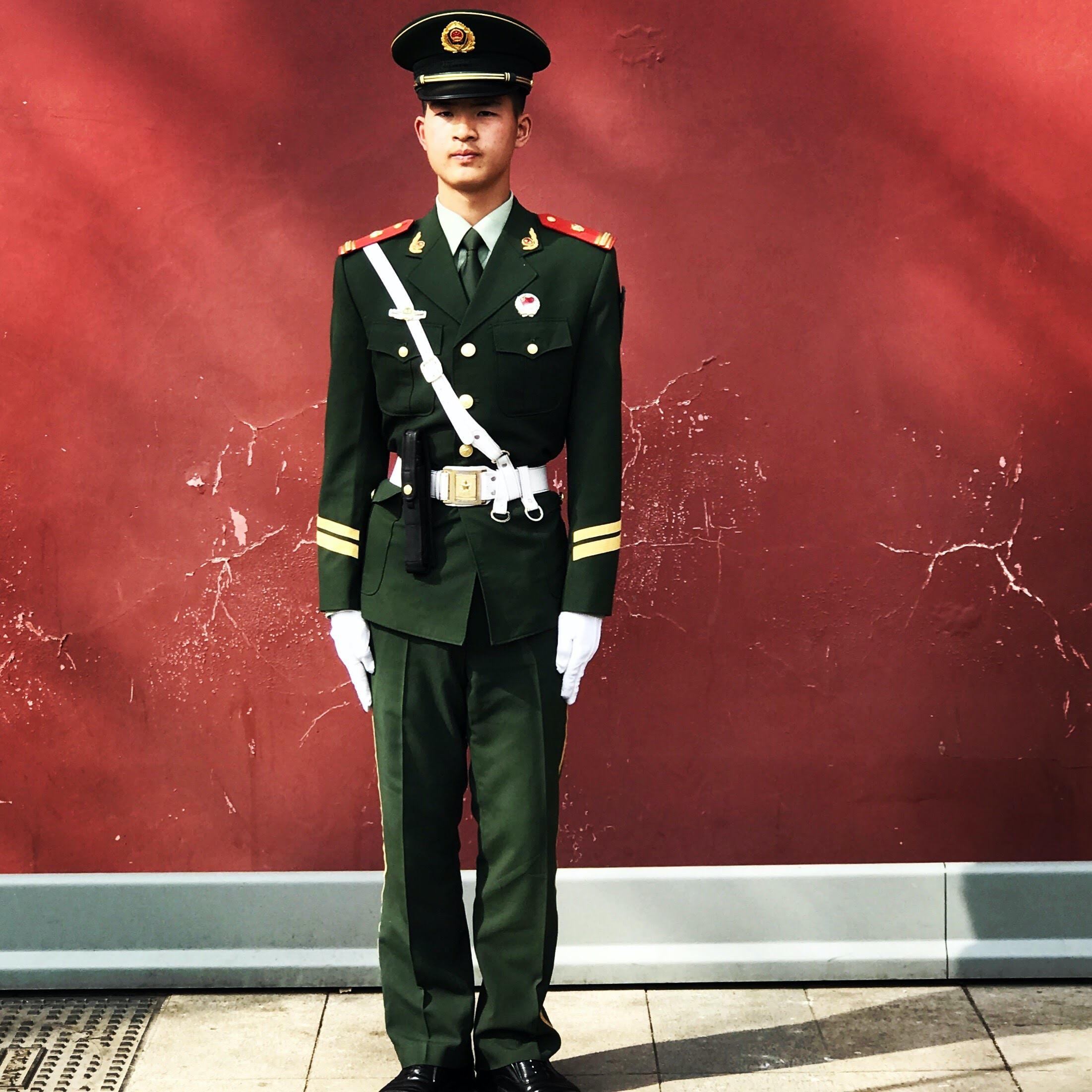 man standing near red wall