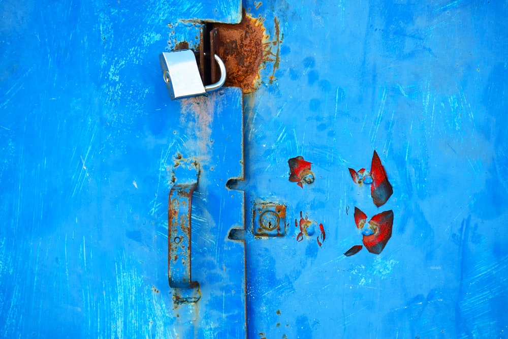 silver padlock on blue steel door